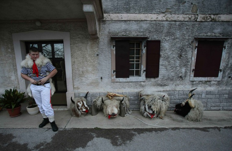"A bell ringer, or ""Zvoncari"", stands next to masks as he prepares for a parade in the village of Marcelji, Croatia, March 2, 2014. (Antonio Bronic/Reuters)"
