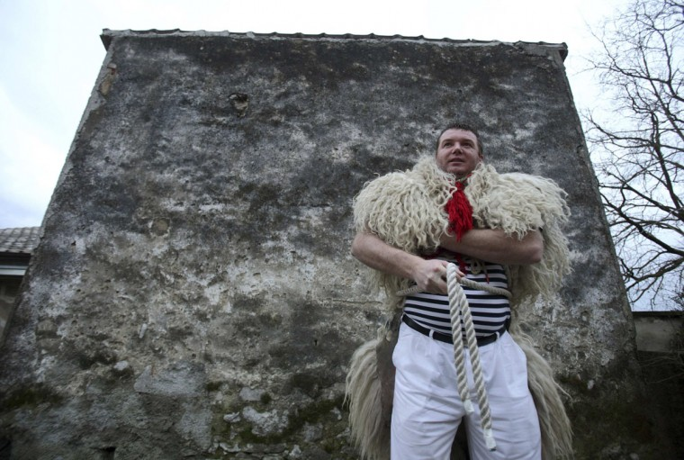 """A bell ringer, or """"Zvoncari"""", prepares for a parade in the village of Marcelji, Croatia, on March 2, 2014. According to traditional customs, the bell ringers would walk through different villages and create huge amounts of noise to scare away evil spirits of winter and welcome spring. Their costumes consist of white trousers and striped shirts, including a sheepskin thrown over their shoulders and a big bell tied around their waist. (Antonio Bronic/Reuters)"""