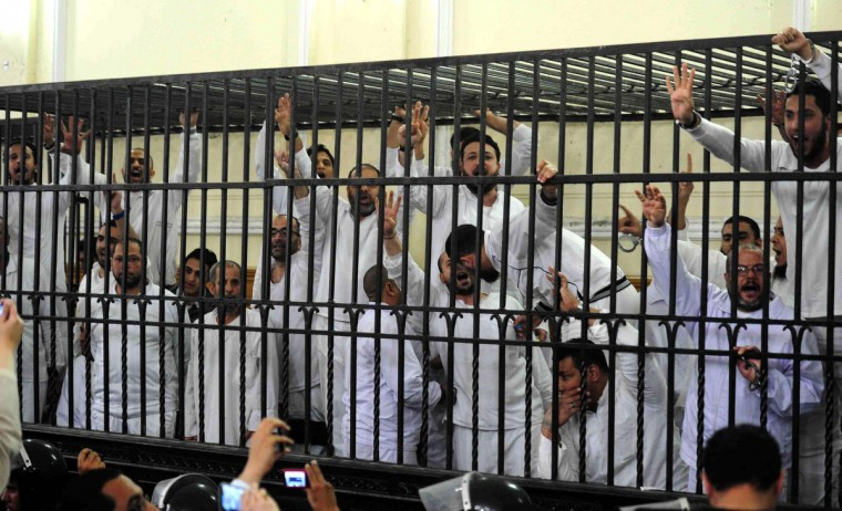 Supporters of former Egyptian president Mohamed Mursi, standing trial on charges of violence that broke out in Alexandria last year, react after two fellow supporters were sentenced to death, in a court in Alexandria, March 29, 2014. (Al Youm / Reuters)