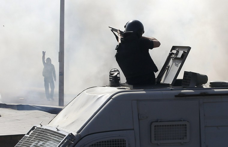A special forces police officer fires rubber bullets as a protester raises his hand during a demonstration at the front of Cairo University. One person was killed near Egypt's Cairo University on Wednesday when protesters supporting ousted President Mohamed Mursi clashed with security forces, a health ministry official told Reuters. The protesters were demonstrating against a court ruling earlier this week condemning more than 500 alleged Muslim Brotherhood supporters to death. (Amr Abdallah Dalsh/Reuters)