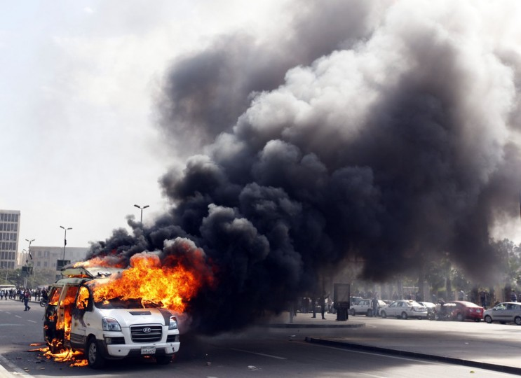 A car belonging to the media burns during a protest by supporters of the Muslim Brotherhood and ousted Egyptian President Mohamed Mursi inside Cairo University, in Cairo, March 9, 2014. (Mohamed Abd El Ghany/Reuters)