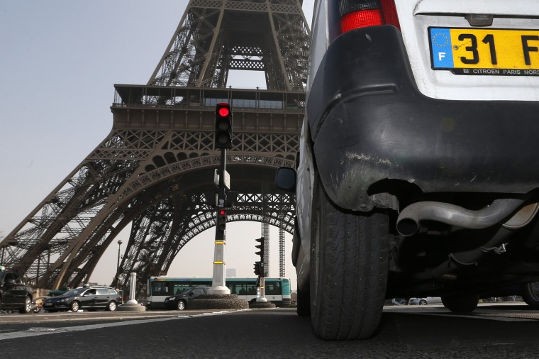 A car drives near the Eiffel tower in Paris, March 14, 2014. Residents and visitors to Paris basking in a streak of unseasonable sunshine were also being treated with a dangerous dose of particles from car fumes that pushed air pollution to levels above other northern European capitals this week. Swathes of France, including the French capital, were on maximum alert over air pollution, prompting Paris authorities to render some public transport free for the day. (REUTERS/Charles Platiau)
