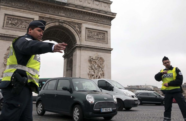 Police officers in Paris control cars with even-numbered licence plates near the Arc de Triomphe March 17. France deployed hundreds of police in Paris on Monday to enforce the most drastic curbs on car use in 20 years as authorities sought to reduce health-endangering pollution days before town hall elections. Amid concerns of a worsening air quality after a week when unseasonally balmy weather boosted pollution, public transport was free of charge while drivers with even-numbered licence plates were told to leave their cars at home or face fines.   || PHOTO CREDIT: PHILIPPE WOJAZER   - REUTERS