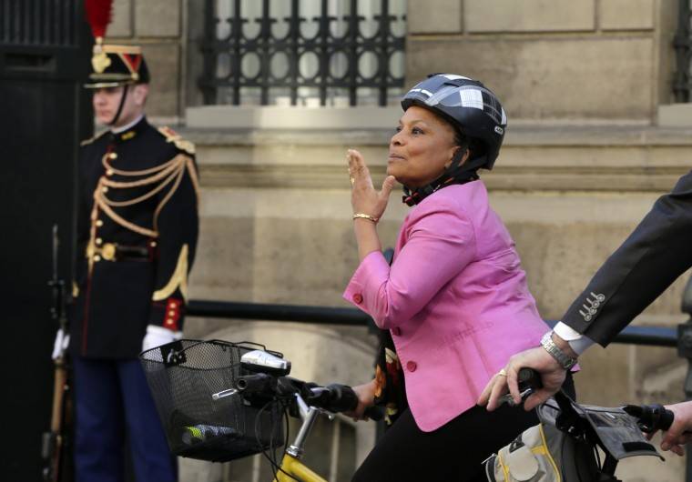 French Justice Minister Christiane Taubira blows a kiss as she leaves the Elysee Palace on a bicycle after a meeting in Paris March 13, 2014. France's justice minister on Wednesday defied calls for her to quit after it emerged that she knew former President Nicolas Sarkozy's phone was being tapped, apparently contradicting an earlier statement from her. (REUTERS/Jacky Naegelen)