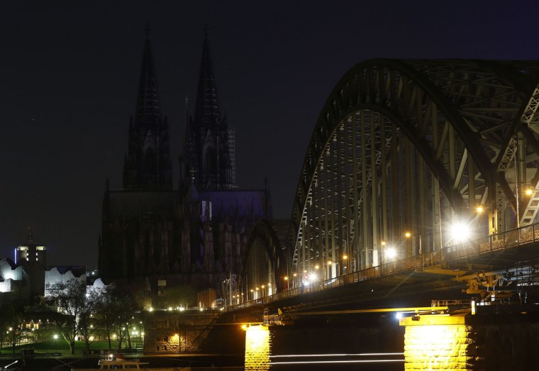 An lighted panel is seen in front of the UNESCO World Heritage Cologne Cathedral and the Hohenzollern railway bridge along the river Rhine before Earth Hour on March 29, 2014. (REUTERS/Ina Fassbender)