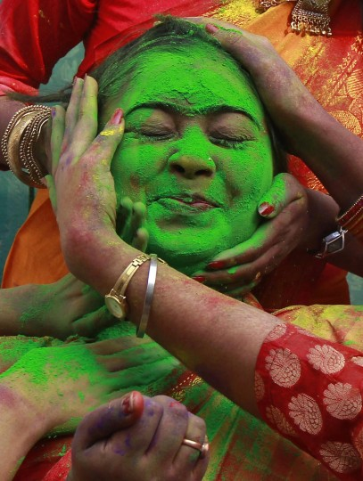 A student of Rabindra Bharati University reacts as her fellow students apply colored powder to her face during celebrations for Holi, also known as the festival of colors in Kolkata March 12, 2014. The traditional event heralds the beginning of spring and is celebrated all over India. (Rupak De Chowdhuri/Reuters)