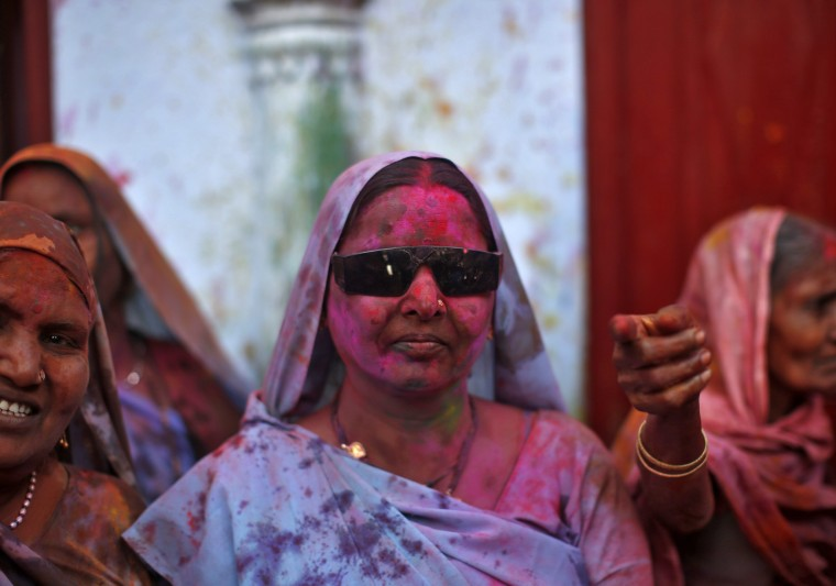 A woman, who is a former scavenger, watches with her face smeared with coloured powder during the Holi celebrations organised by non-governmental organisation Sulabh International at a widows' ashram in Vrindavan in the northern Indian state of Uttar Pradesh March 14, 2014. Holi, also known as the Festival of Colours, heralds the beginning of spring and is celebrated all over India. (REUTERS/Ahmad Masood)