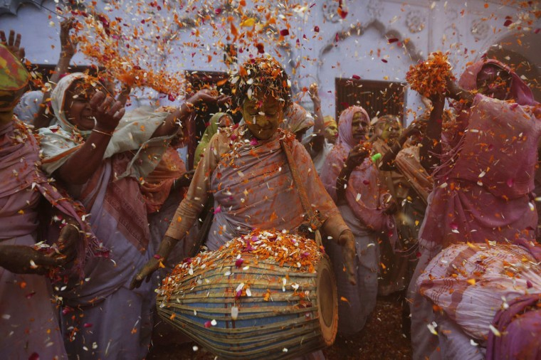 Widows dance as they throw flowers into the air during Holi celebrations organized by non-governmental organisation Sulabh International at a widows' ashram in Vrindavan in the northern Indian state of Uttar Pradesh, March 17, 2014. (Adnan Abidi/Reuters)