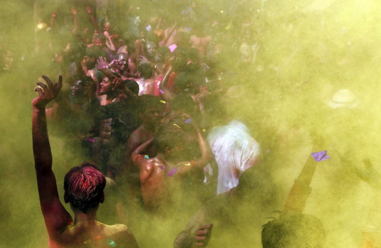 Men dance as coloured powder is sprayed on them during Holi celebrations in the northern Indian city of Allahabad March 18, 2014. Holi, also known as the Festival of Colours, heralds the beginning of spring and is celebrated all over India. (Jitendra Prakash/Reuters)