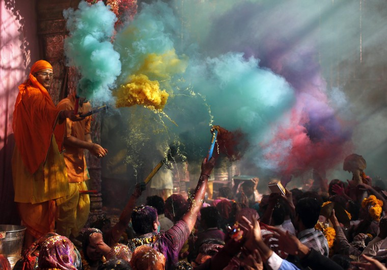 Hindu priests throws coloured powder at the devotees during Holi celebrations at Bankey Bihari temple in Vrindavan, in the northern Indian state of Uttar Pradesh, March 13, 2014. Holi, also known as the Festival of Colours, heralds the beginning of spring and is celebrated all over India. (REUTERS/Ahmad Masood)