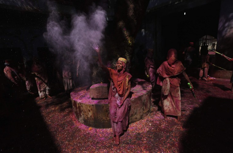 A widow throws colored powder into the air during Holi celebrations organised by non-governmental organization Sulabh International at a widows' ashram in Vrindavan in the northern Indian state of Uttar Pradesh March 17, 2014. Traditionally in Hindu culture, widows are expected to renounce earthly pleasure, so they do not celebrate Holi. But women at the shelter for widows, who have been abandoned by their families, celebrated the festival by throwing flowers and colored powder. (Adnan Abidi/Reuters)