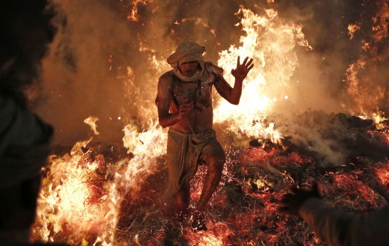Hindu priest Babulal jumps out of a fire to signify the burning of the demon Holika during a ritual to mark the first day of the Holi spring festival, also known as the Festival of Colors, at village Phalen near the northern Indian city of Mathura, March 17, 2014. Holi in Phalen starts on the first day of the full moon, where a Hindu mythological story will be re-enacted to symbolize the victory of good over evil, according to local media. (Adnan Abidi/Reuters)