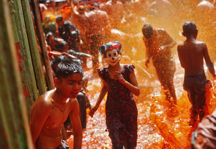 """A girl wearing a mask runs as boys splash coloured water on her during """"Huranga"""" at Dauji temple, near the northern Indian city of Mathura March 18, 2014. Huranga is a game played between men and women a day after Holi, the festival of colours, during which men drench women with liquid colours and women tear off the clothes of the men. (Anindito Mukherjee/Reuters)"""