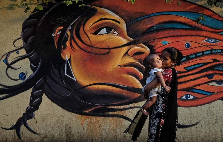 A mother kisses her child as she walks past graffiti in Mumbai March 27, 2014.(Danish Siddiqui/Reuters)