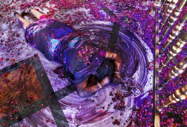 A Hindu woman prays while lying on the floor of a temple during Holi celebrations in the western Indian city of Ahmedabad, March 17, 2014. (Amit Dave/Reuters)