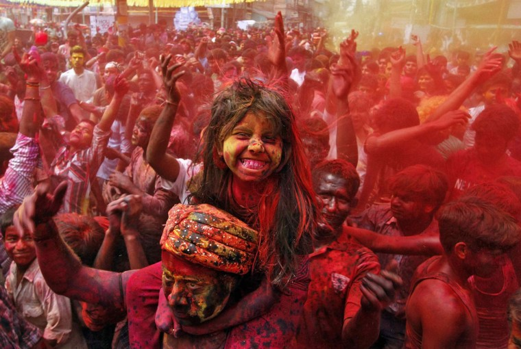 A girl sits on her father's shoulders and cheers as she and others daubed in colors dance while celebrating Holi in the northeastern Indian city of Guwahati, March 17, 2014. (Utpal Baruah/Reuters)