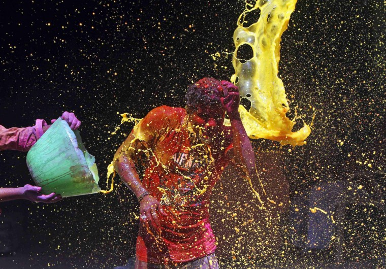 A man reacts to colored water being splashed over him during Holi celebrations in the southern Indian city of Chennai, March 17, 2014. Holi, also known as the Festival of Colors, heralds the beginning of spring and is celebrated all over India. (Babu/Reuters)