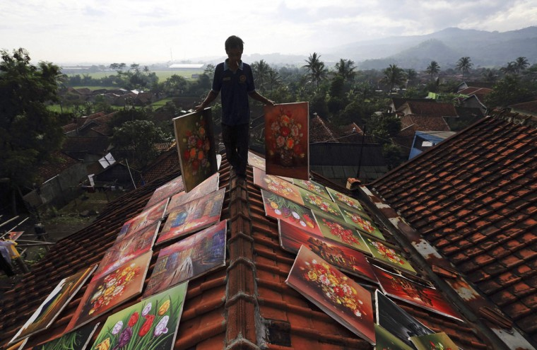 An artist walks across the roof of his house while carrying paintings to be dried at Jelekong village near Bandung, in Indonesia's West Java province, March 20, 2014. The people of Jelekong village earn their living by selling their paintings. Around 300 painters live in the village, producing about 1,000 paintings a month, each priced between 50,000 rupiah to 11,000,000 rupiah ($4.50 to $1000), according to villager Asep Sancang, who works as a high school art teacher and painter. (REUTERS/Beawihart)