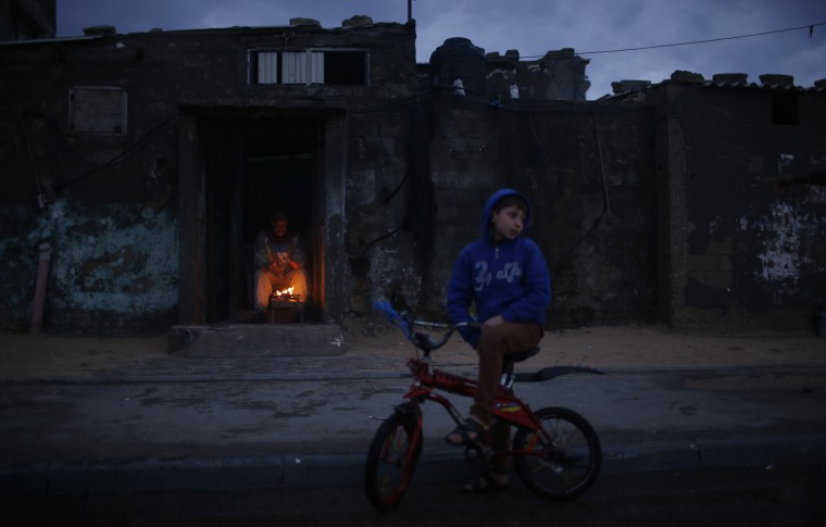 A Palestinian man warms himself by a fire inside his house at Shati refugee camp in Gaza City March 13, 2014. (REUTERS/Mohammed Salem)
