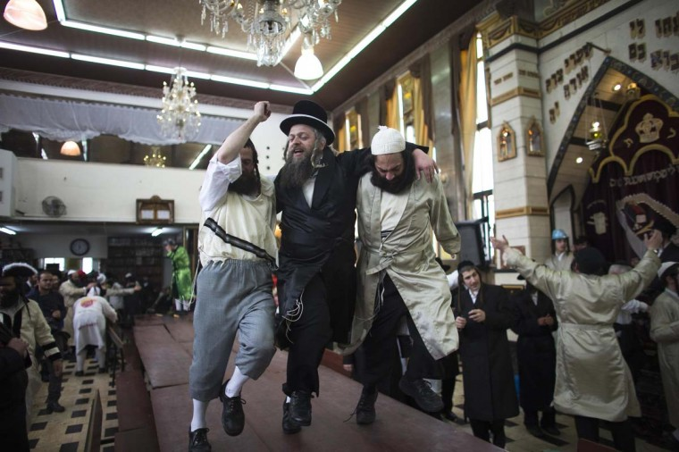 Ultra-Orthodox Jewish men dance on a table as they celebrate the holiday of Purim in Jerusalem's Mea Shearim neighbourhood March 17.|| PHOTO CREDIT: RONEN ZVULUN  - REUTERS