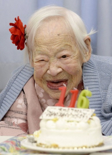Japanese Misao Okawa, the world's oldest woman, poses for a photo next to her birthday cake as she celebrates her 116th birthday in Osaka, western Japan, in this photo taken by Kyodo. Okawa celebrated her 116th birthday on Wednesday. (Kyodo/Reuters)