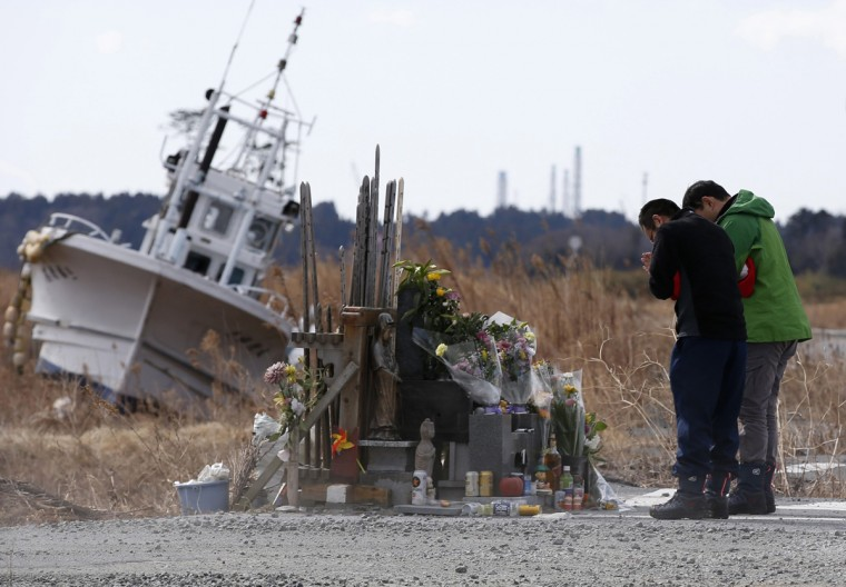 People pray for victims of the March 11, 2011 earthquake and tsunami as Tokyo Electric Power Co's (TEPCO) tsunami-crippled Fukushima Daiichi nuclear power plant is seen in the background at Namie town, Fukushima prefecture March 11, 2014. Tuesday marks the third year anniversary of the March 11, 2011 earthquake and tsunami that killed thousands and set off a nuclear crisis. (Toru Hanai/Reuters)