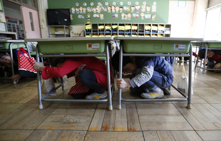 Students take shelter under desks during an earthquake simulation exercise at an elementary school in Tokyo March 11, 2014. Schools in Chiyoda ward, one of the central wards in Tokyo, held an annual evacuation drill to prepare for a major earthquake in Tokyo, on the day of the third anniversary of the March 11, 2011 earthquake and tsunami that killed thousands. About 5,000 students participated in the exercises in Chiyoda ward, the official says. (Yuya Shino/Reuters)