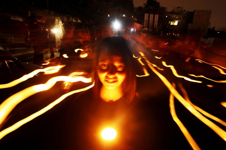 People hold candles during Earth Hour after the lights were turned off in central Amman, Jordan on March 29, 2014. (REUTERS/Ali Jarekji)