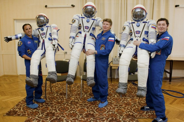 From left, International Space Station (ISS) crew members Joseph Acaba (U.S.) and Russian cosmonauts Gennady Padalka and Sergei Revin demonstrate their space suits at the Baikonur cosmodrome May 3, 2012. (REUTERS/Sergei Remezov)