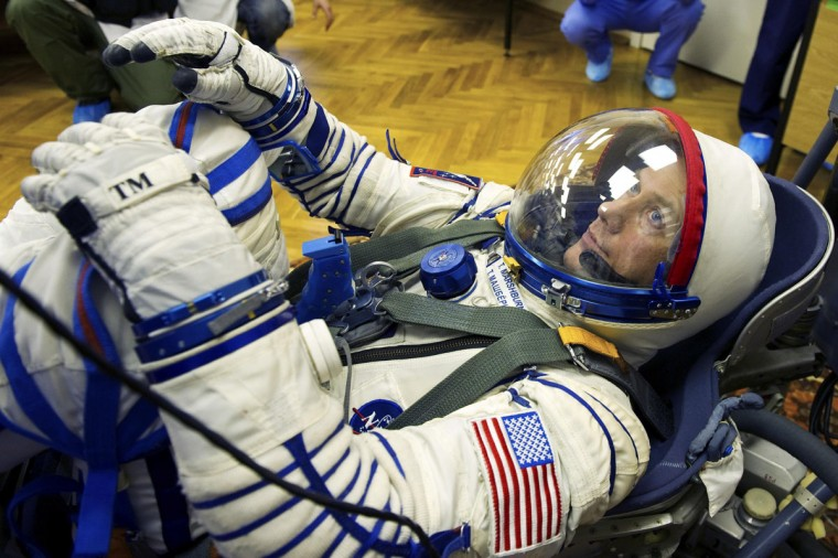 International Space Station (ISS) crew member Thomas Marshburn waits as specialists check his suit at Baikonur cosmodrome on December 7, 2012. (REUTERS/Sergei Remezov)