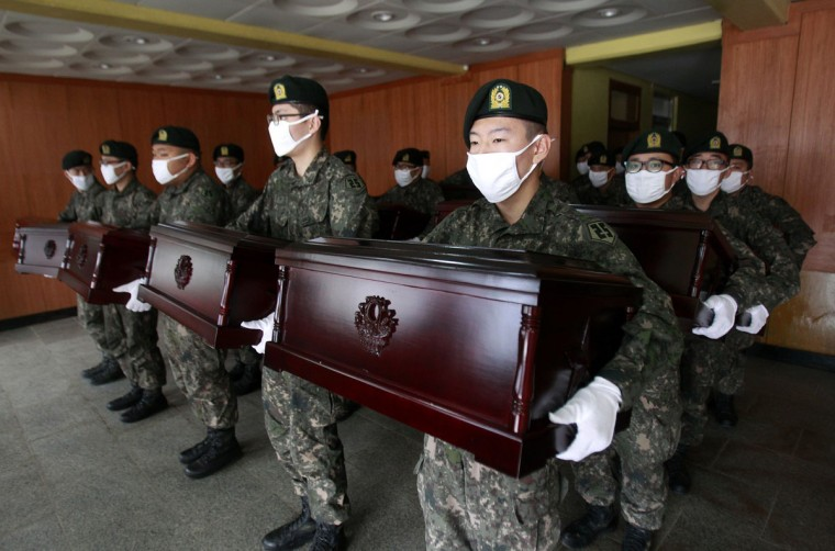 South Korean army soldiers hold caskets containing the remains of Chinese soldiers to be transported to Incheon International Airport, at the temporary columbarium in Paju March 27, 2014. The remains of 437 Chinese soldiers killed during the 1950-53 Korean War were transferred from the temporary columbarium in South Korea to the airport on Thursday to be returned to China. (Ahn Young-joon/Reuters)