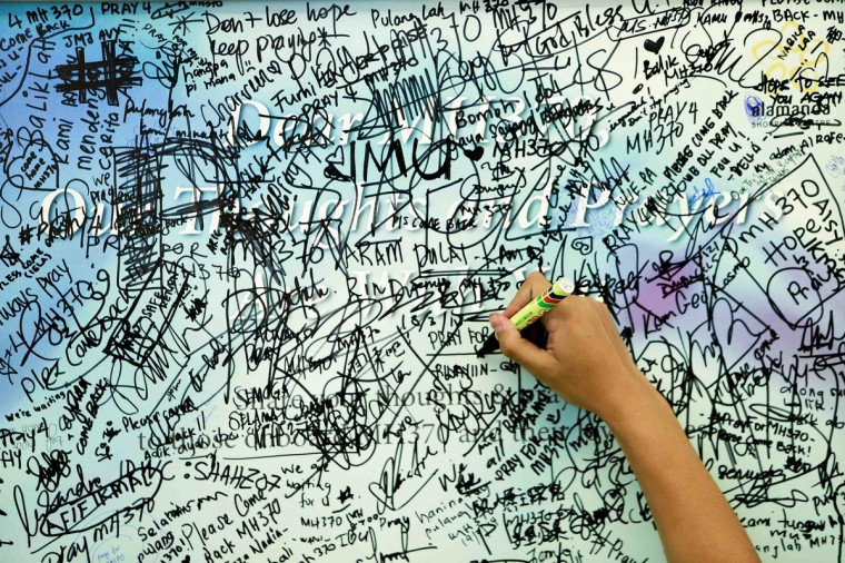 A man writes messages and well-wishes for family members of passengers onboard the missing Malaysia Airlines Flight MH370 inside a shopping mall in Putrajaya, March 20, 2014. (Samsul Said/Reuters photo)