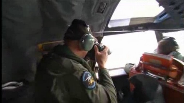 "A crewman looks out of the window on board Royal Australian Air Force (RAAF) P3 Orion aircraft during a sea search for the missing Malaysia Airlines flight MH370 in an area between Australia, southern Africa and Antarctica, in this still image taken from video March 20, 2014. Aircraft and ships plowed through dire weather on Thursday in search of objects floating in remote seas off Australia that Malaysia's government called a ""credible lead"" in the trans-continental hunt for a jetliner missing for nearly two weeks. (via Reuters TV)"