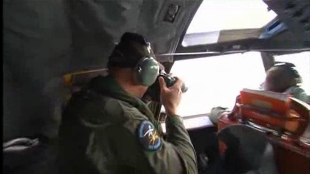 A crewman looks out of the window on board RAAF P3 Orion aircraft