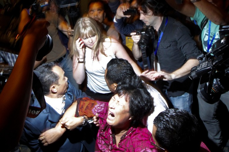 A Chinese family member of a passenger onboard the missing Malaysia Airlines Flight MH370 screams as she is being brought into a room outside the media conference area at a hotel in Kuala Lumpur International Airport. Investigators probing the disappearance of Flight MH370 with 239 people on board believe it most likely flew into the southern Indian Ocean, a source close to the investigation said on Wednesday. (Edgar Su/Reuters)