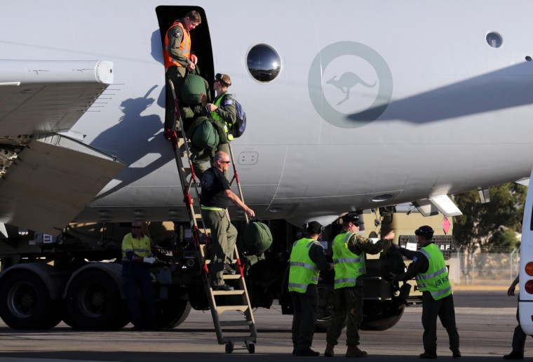 Royal Australian Air Force (RAAF) crew members from of an AP-3C Orion maritime patrol aircraft walk down a ladder after they arrived in Perth March 20, 2014 after searching an area in the southern Indian Ocean for the Malaysia Airlines flight MH370. (Tony Turner/Reuters photo)