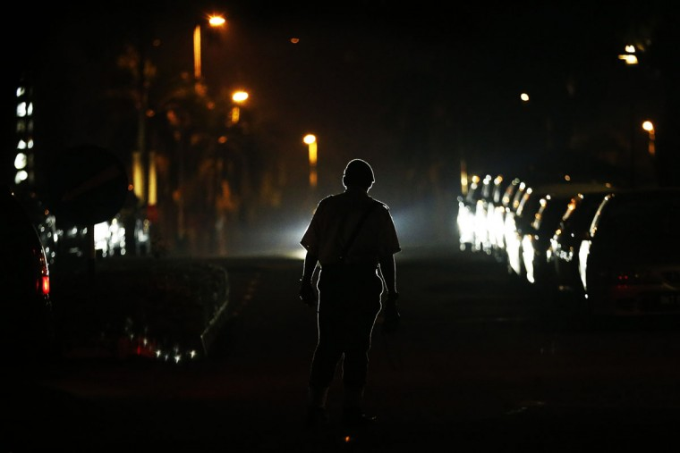 "A security guard stands on the road near the hotel where family members of missing Malaysia Airlines flight MH370 passengers gather for a briefing on the current situation in Cyberjaya, outside Kuala Lumpur March 20, 2014. Aircraft and ships ploughed through dire weather on Thursday in search of objects floating in remote seas off Australia that Malaysia's government called a ""credible lead"" in the trans-continental hunt for a jetliner missing for nearly two weeks. (REUTERS/Damir Sagolj)"