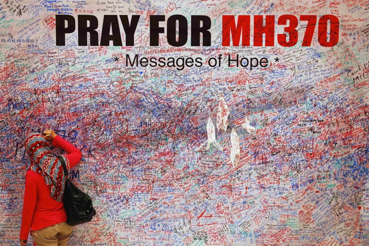 A woman leaves a messages of support and hope for the passengers of the missing Malaysia Airlines MH370 in central Kuala Lumpur March 16, 2014. Police are combing through the personal, political and religious backgrounds of pilots and crew of the missing Malaysian jetliner, a senior officer said on Sunday, trying to work out why someone aboard flew the plane hundreds of miles off course. (Damir Sagolj/Reuters)