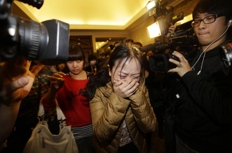 A relative (front) of a passenger of Malaysia Airlines flight MH370 cries as she walks past journalists at a hotel in Beijing, March 9, 2014. The Malaysia Airlines Boeing 777-200ER aircraft carrying 227 passengers and 12 crew was presumed to have crashed off the Vietnamese coast on Saturday. (Jason Lee/Reuters)