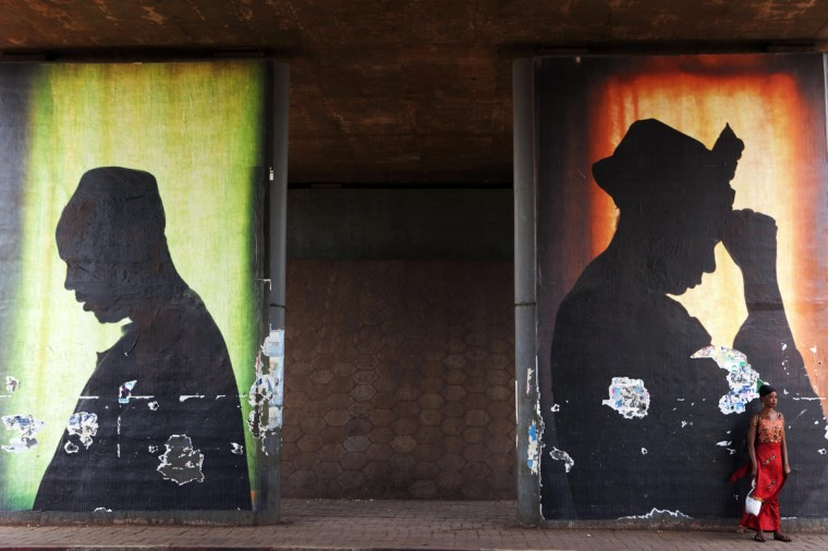 Posters tower over a woman stands in front of a poster in Bamako, Mali. (Joe Penney/Reuters)
