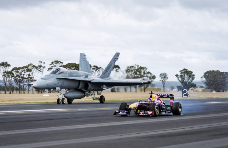 Formula One driver Daniel Ricciardo of Australia races alongside a Royal Australian Air Force F/A-18 Hornet during a promotional event near Melbourne in this handout photo provided by Red Bull. The Australian Formula One Grand Prix will be held on March 16. (Handout/Reuters)