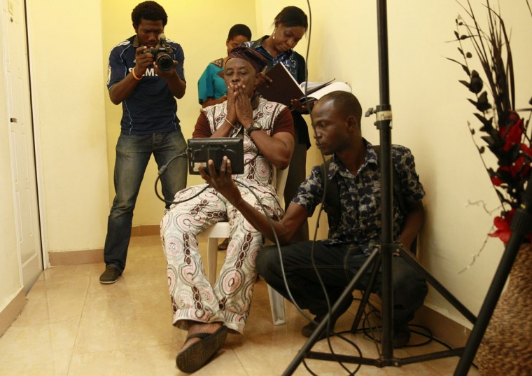 "Nigerian director Tunde Kelani (seated) watches a monitor as he directs a scene during the filming of ""Dazzling Mirage"" at a location in the outskirt of Lagos, September 9, 2013. (Akintunde Akinleye/Reuters)"