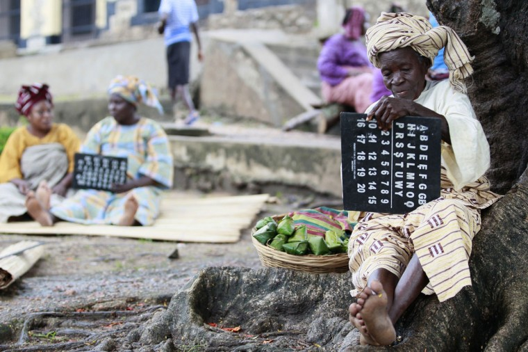 "An actress holds a slate as she performs a scene during the making of ""Ake"", a film based on the childhood memoirs of Nigerian writer Wole Soyinka, in Abeokuta, southwest Nigeria, July 15, 2013. (Akintunde Akinleye/Reuters)"