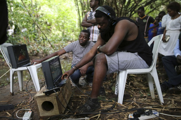 "Director Kunle Afolayan watches a monitor while directing a scene during the filming of police thriller ""October 1"" at a rural location in Ilaramokin village, southwest Nigeria, August 24, 2013. (Akintunde Akinleye/Reuters)"