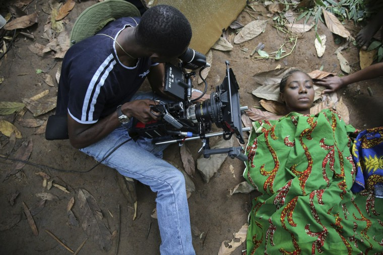 "A cameraman films a scene for the movie ""October 1"", a police thriller directed by Kunle Afolayan, at a rural location in Ilaramokin village, southwest Nigeria, August 24, 2013. (Akintunde Akinleye/Reuters)"