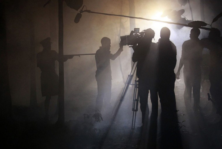 "Actors perform a scene at night while filming ""October 1"", a police thriller directed by Kunle Afolayan, at a rural location in Akure, southwest Nigeria, August 26, 2013. Nigeria's movie business, often known as Nollywood, is one of the biggest in the world. Most films are produced in local languages - Yoruba, Hausa and Igbo among them - while many others are made in English. Nollywood also has a growing audience among Africans living abroad, keen for a taste of home, whether watched in south London hairdressers or rented from Texas video stores. Nigeria shot its first film, ""Palaver"" (Trouble), in 1904. Picture taken August 26, 2013. (Akintunde Akinleye/Reuters)"