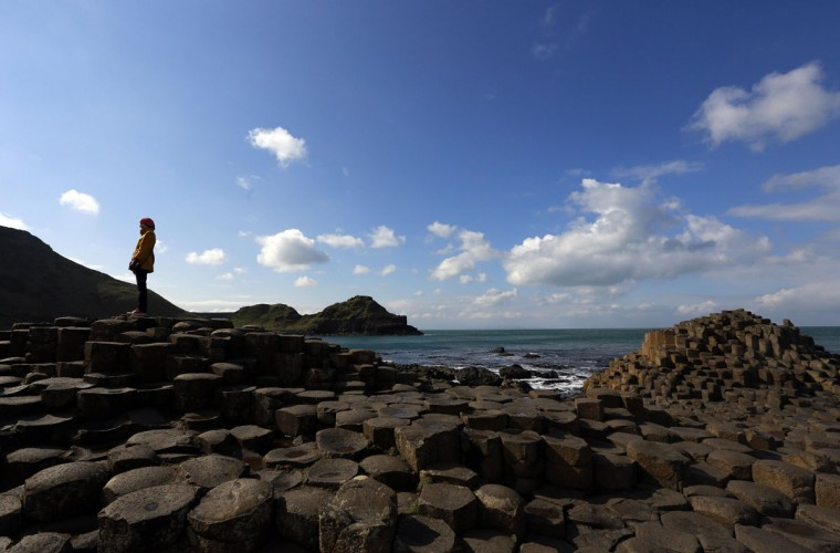 A woman poses for a picture on the rocks at the Giant's Causeway situated on the north coast of Northern Ireland. March 27, 2014. A new book by Lonely Planet reveals the top 50 must-see world wonders with the Giant's Causeway featuring high on the list. (Cathal McNaughton/Reuters)