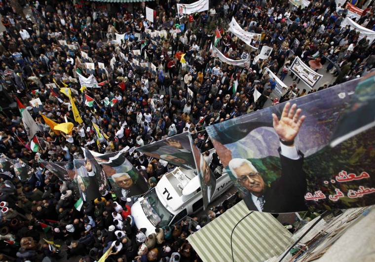 Banners depicting Palestinian President Mahmoud Abbas hang over the crowd during a rally in the West Bank city of Ramallah March 17. Thousands of Palestinians took to the streets on Monday to show their support for Abbas, who is under heavy pressure as he prepares to meet U.S. President Barack Obama.  || PHOTO CREDIT: MOHAMAD TOROKMAN  - REUTERS
