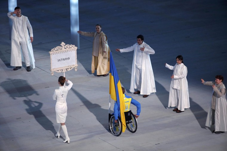 Ukraine's flag-bearer Mykhaylo Tkachenko arrives in the stadium during the opening ceremony of the 2014 Paralympic Winter Games in Sochi, March 7, 2014. (REUTERS/Christian Hartmann)