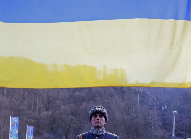 A Russian soldier looks at a Ukrainian flag during a medal ceremony at the 2014 Sochi Paralympic Winter Games in Rosa Khutor, March 9, 2014. (REUTERS/Alexander Demianchuk)